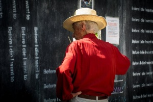 "Monty adding his own vision to the ""Before I die"" wall on Biltmore Avenue - photo taken August 22nd.  Monty said that he didn't like some things about himself - like how judgmental he was of others - but that he never got down on himself for it, never felt bad about himself, never felt guilty.  I don't know how he pulled this off - I couldn't - but I believe he did.  When he walked through that final door, I'm sure he did it with no regrets."